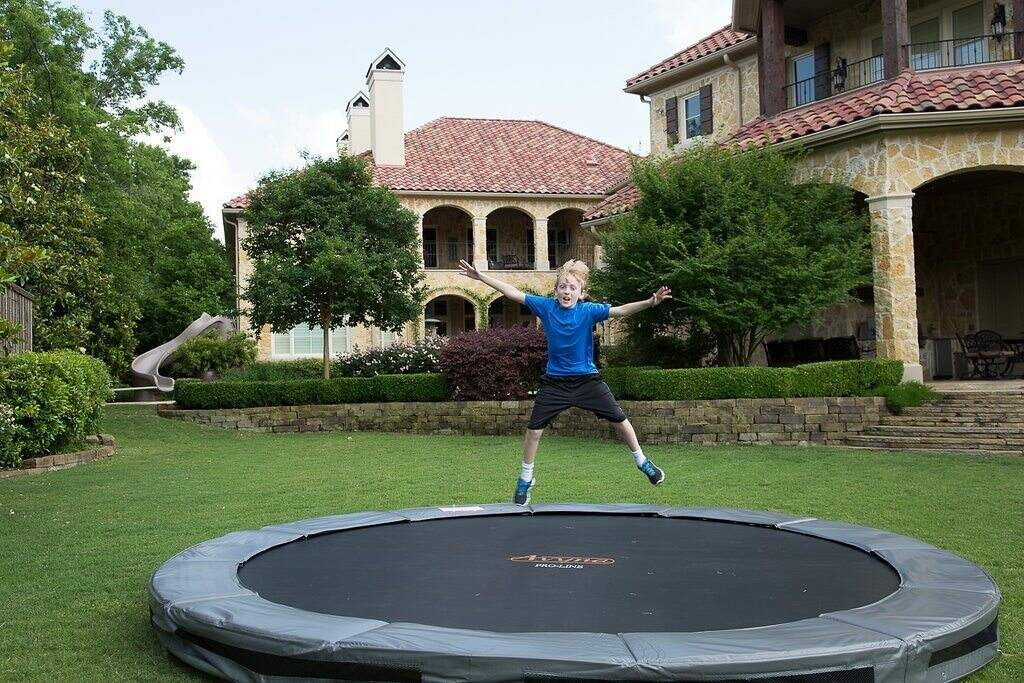 A child jumping on an inground trampoline