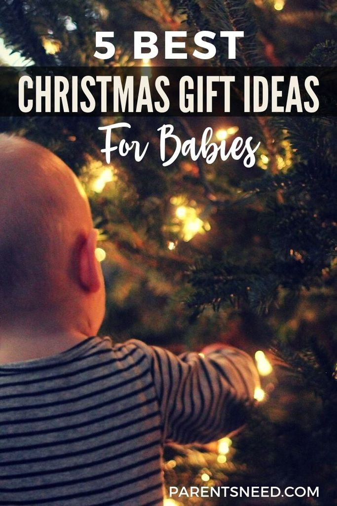 A baby reaching with wonder towards a Christmas tree
