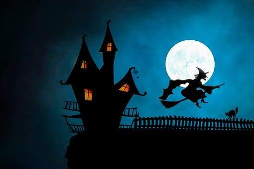silhouette of haunted house and witch on broomstick